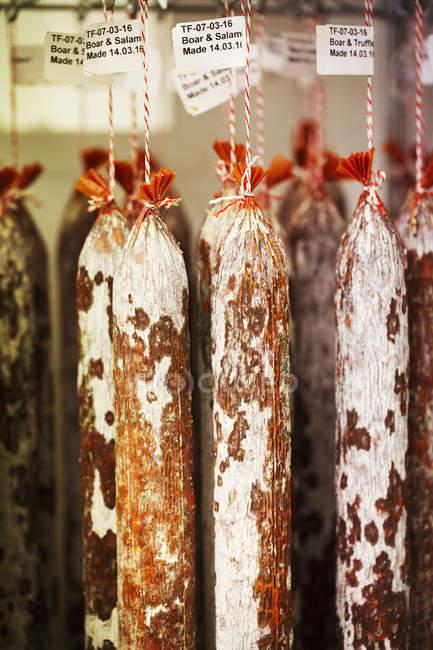 Chorizos que cuelgan de ganchos - foto de stock