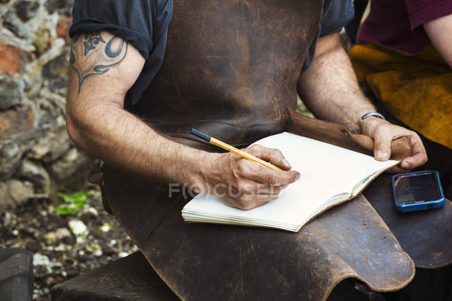 Man writing into a notebook — Stock Photo