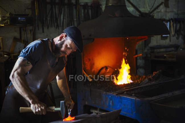Blacksmith strikes a pieces of hot metal — Stock Photo