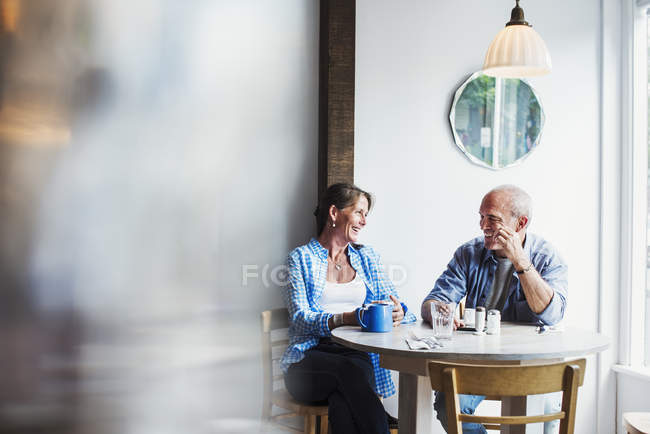 People seated at a coffee shop table. — Stock Photo