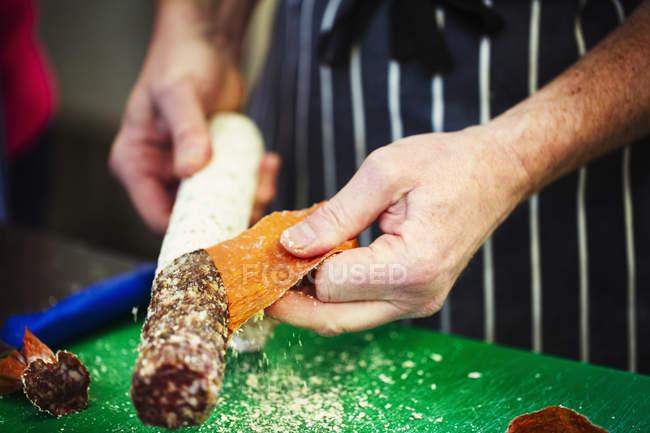 Carnicero tomando piel de salami - foto de stock