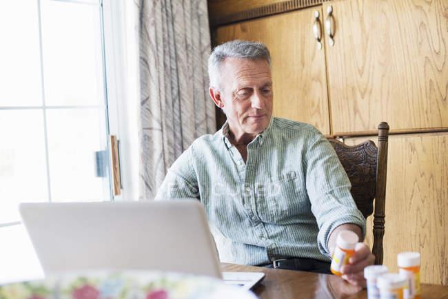 Hombre mayor usando un ordenador portátil - foto de stock
