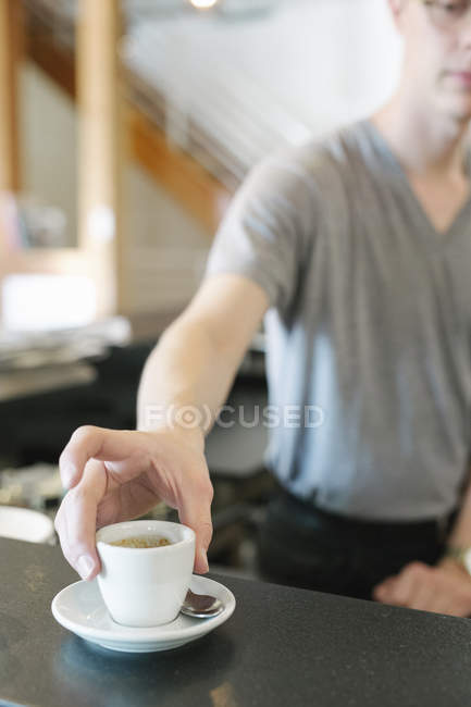 Man standing at a counter in a coffee shop — Stock Photo