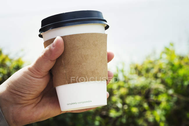 Человеческая рука с одноразовой бумажной чашкой — стоковое фото