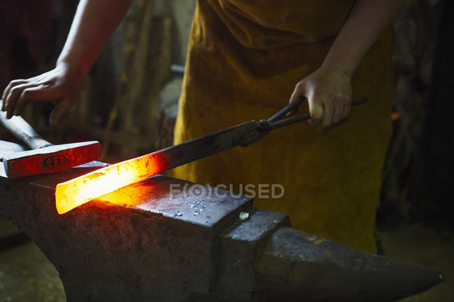 Blacksmith holds a length of hot metal — Stock Photo