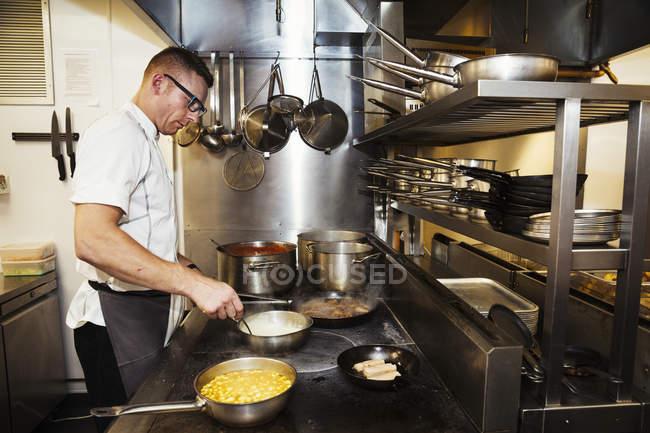 Homme chef cuisinier dans une cuisine — Photo de stock