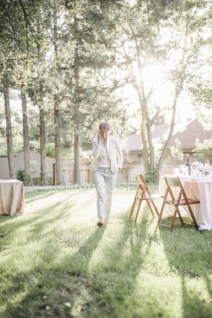 Woman standing in a sunlit garden — Stock Photo