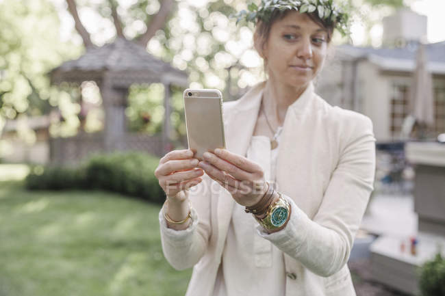Woman with a flower wreath taking a selfie — Stock Photo