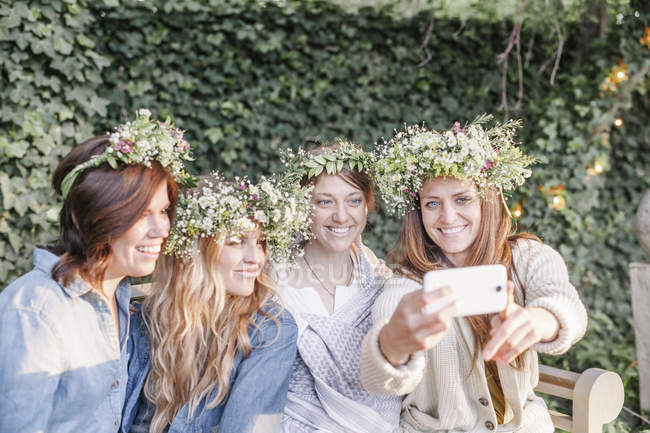 Women with a flower wreaths taking a selfie. — Stock Photo