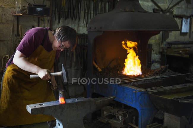 Blacksmith strikes a length of hot metal — Stock Photo