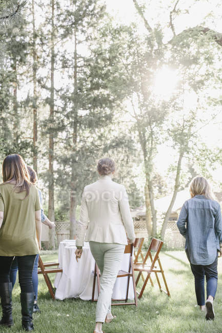 Three women walking towards a table — Stock Photo