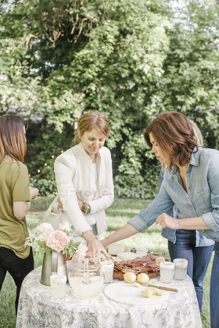Women with food and drinks in a garden. — Stock Photo