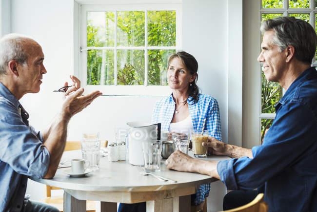 Männer und eine Frau in Coffee-shop — Stockfoto