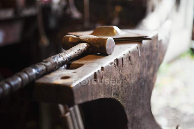 Metal hammer lying on an anvil — Stock Photo