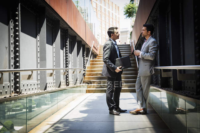 Businessmen standing outdoors and talking — Stock Photo