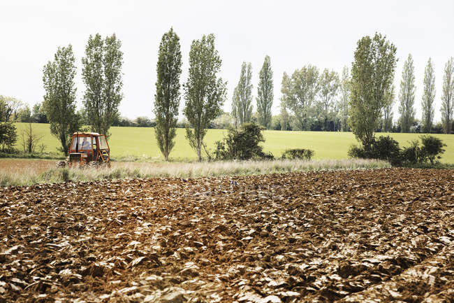 Campo lavrado e um trator em movimento. — Fotografia de Stock