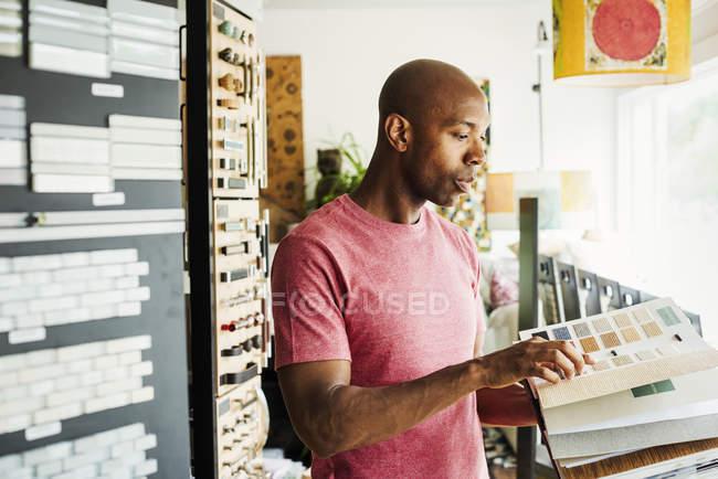 Man looking at a sample book — Stock Photo