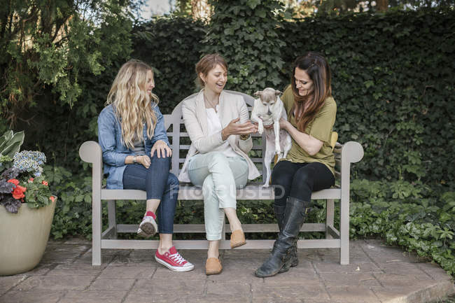 Women with dog sitting on a bench in a garden — Stock Photo