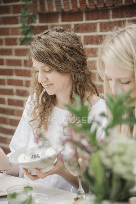 Women outside a house having a meal. — Stock Photo