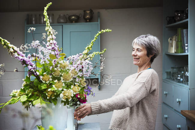 Female florist working with flowers — Stock Photo