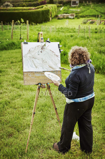 Woman artist standing outdoors at an easel — Stock Photo