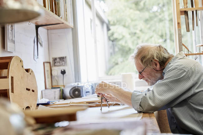 Violin maker at drawing board — Stock Photo