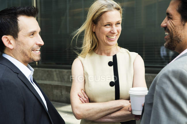 Businesswoman and two businessmen chatting and smiling — Stock Photo