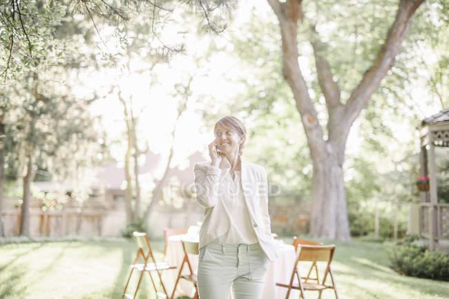 Woman standing in a sunlit garden — Stock Photo