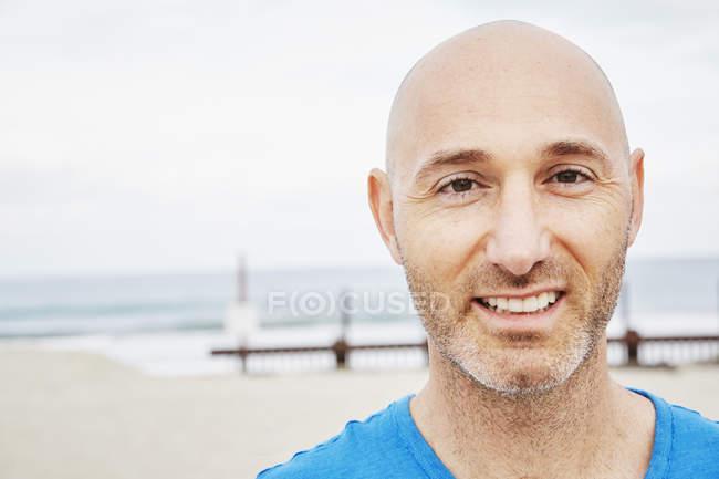 Chauve mature homme debout sur une plage — Photo de stock