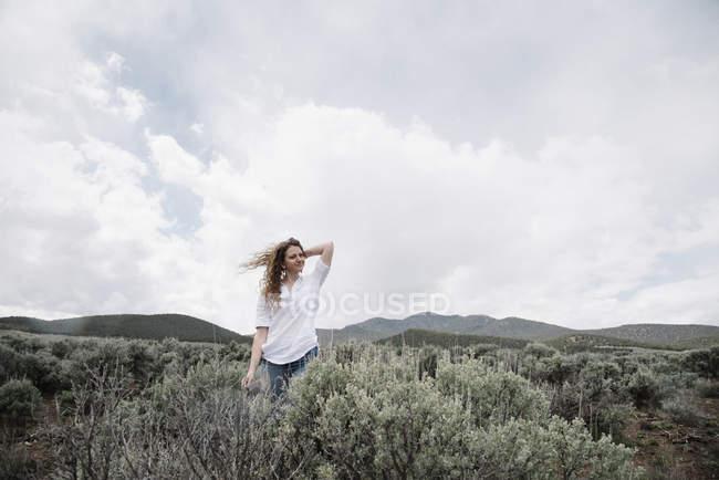 Frau steht in einer offenen Landschaft — Stockfoto