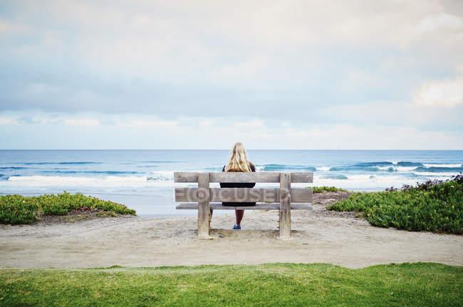 Frau sitzt an einem Strand am Meer. — Stockfoto