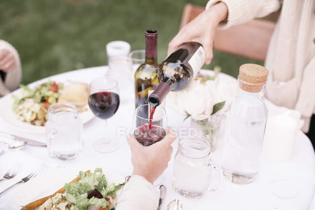 Woman pouring a glass of red wine. — Stock Photo