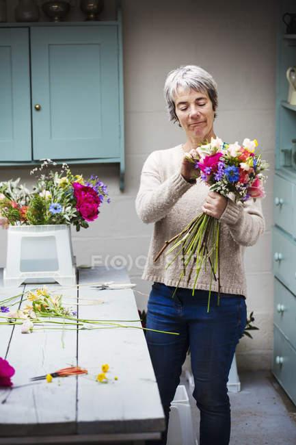 Fiorista creando un mazzo di fiori freschi . — Foto stock