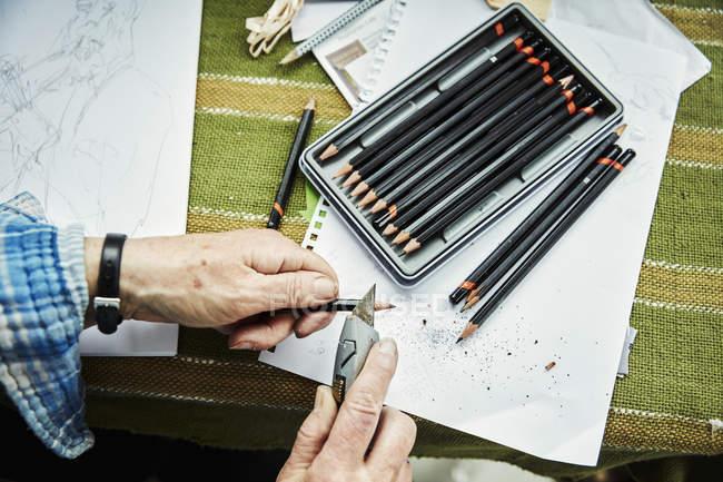 Frau spitzt Bleistifte mit Bastelmesser — Stockfoto