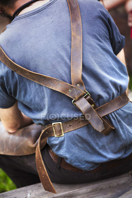 Leather straps of a man's metalworking apron. — Stock Photo