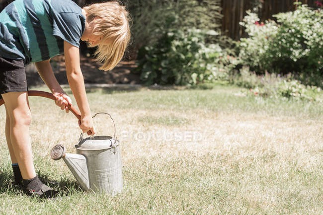 Boy filling watering can — Stock Photo