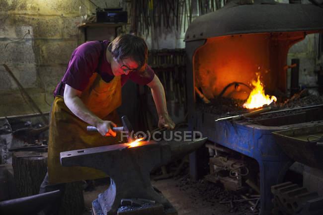 Blacksmith striking red hot metal — Stock Photo