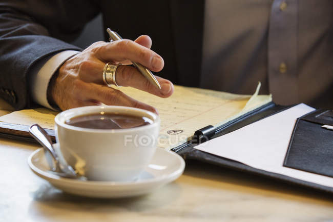 Businessman sitting in cafe with documents — Stock Photo