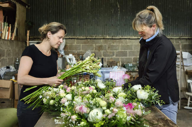 Women at workbench creating floral decorations — Stock Photo