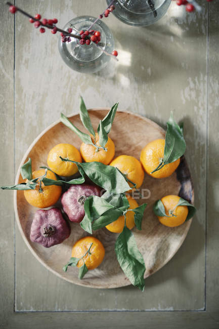 Wooden bowl of oranges — Stock Photo