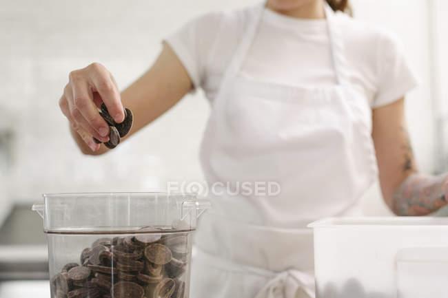 Femme pesant du chocolat en boulangerie — Photo de stock