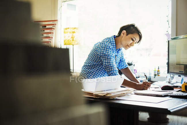 Woman working at desk in interior studio — Stock Photo