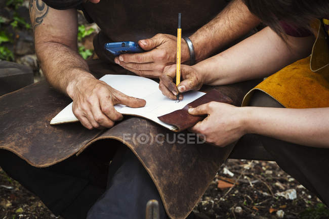 Man and woman writing into a notebook — Stock Photo