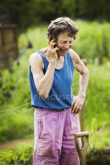 Женщина разговаривает по телефону на ферме — стоковое фото