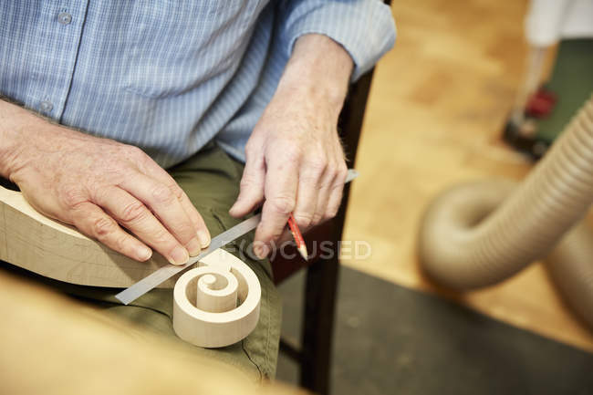 Violin maker using ruler to measure scroll — Stock Photo