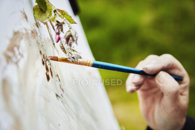 Artista aplicando tinta ao papel com escova — Fotografia de Stock