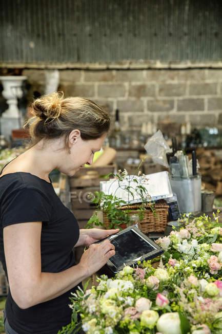 Флорист работает с помощью цифрового планшета — стоковое фото