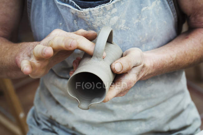 Potter handling a wet clay pot — Stock Photo