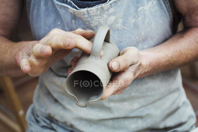 Oleiro manuseando um pote de barro molhado — Fotografia de Stock