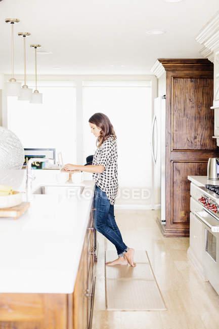 Donna in piedi in una cucina . — Foto stock